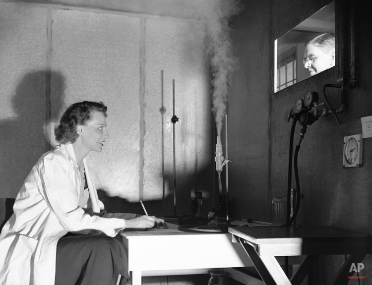 In a laboratory test chamber, Phyllis Ullman, volunteer test subject, records her reactions in simulated smog conditions, while being observed by Paul L. Magill, Stanford University senior chemical engineer, through a window, April 19, 1949. Miss Ullman makes notes on eye and throat irritation as smog is introduced (center of picture). (AP Photo/Ernest K. Bennett)