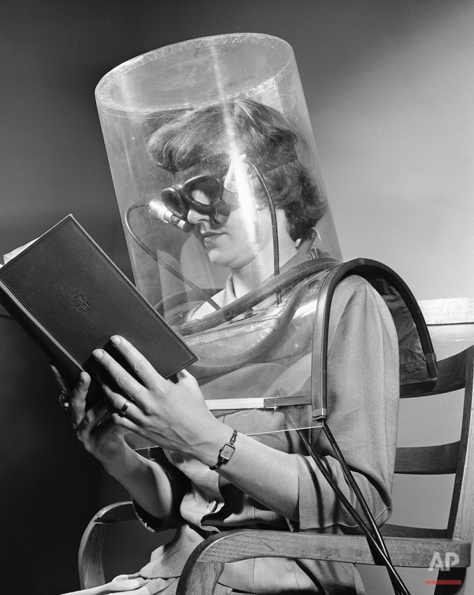 """Betty Cook, a lab assistant at the Stanford Research Institute, is shown taking a """"blink test"""" as part of a project to study smog in Stanford, Calif. April 27, 1949. The test gauges eye irritation through photoelectric cells which record each blink of the eyes. The plastic helmet is filled with measured amounts of smog. Mrs. Cook wears glassless goggles which act as blink recorders. She reads a book to give uniform reaction conditions.The smog project is being conducted by the Air and Water Pollution Laboratory and Fumes of the Western Oil and Gas Association. (AP Photo/Ernest K. Bennett)"""