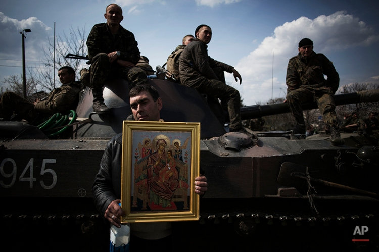 A local resident holds an Orthodox icon in front of an armored vehicle and soldiers of the Ukrainian Army, as they are blocked by people on their way to the town of Kramatorsk on Wednesday, April 16, 2014. Pro-Russian insurgents commandeered six Ukrainian armored vehicles along with their crews and hoisted Russian flags over them Wednesday, dampening the central government's hopes of re-establishing control over restive eastern Ukraine. (AP Photo/Manu Brabo)