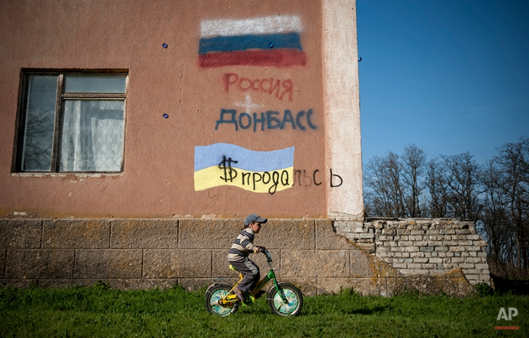 """A boy rides a bicycle past a building with Russian and Ukrainian national flags and words reading """"Ukraine had sold herself for dollars Russia"""" in Uspenka village, 4 kilometers (2.8 miles) to the Ukrainian-Russian border, Donbas region, Ukraine, Friday, April 18, 2014. Dashing hopes of progress raised by a diplomatic deal in Geneva, pro-Russian insurgents who have occupied government buildings in more than 10 Ukrainian cities said Friday they will not leave them until the country's interim government resigns. (AP Photo/Evgeniy Maloletka)"""