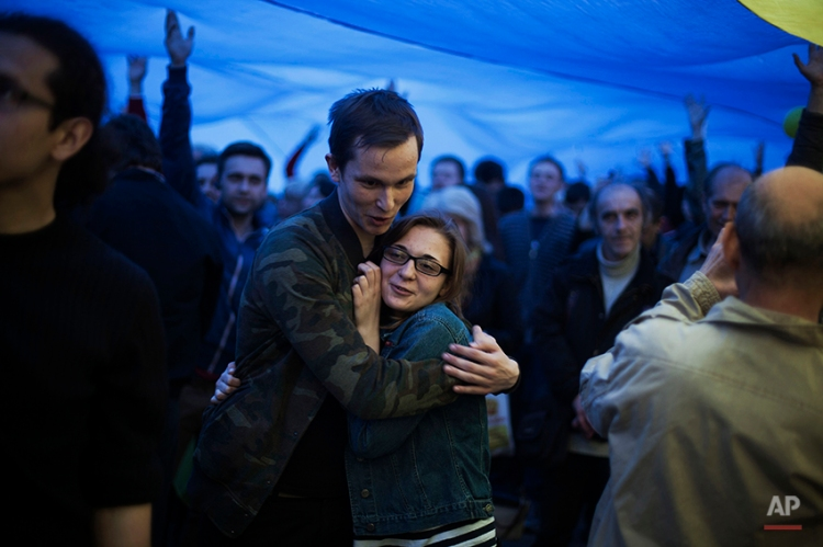 A Ukrainian couple embrace during a pro Ukrainian demonstration in Donetsk, Ukraine, Thursday, April 17, 2014. Top diplomats from the United States, European Union, Russia and Ukraine reached agreement after marathon talks Thursday on immediate steps to ease the crisis in Ukraine. (AP Photo/Manu Brabo)