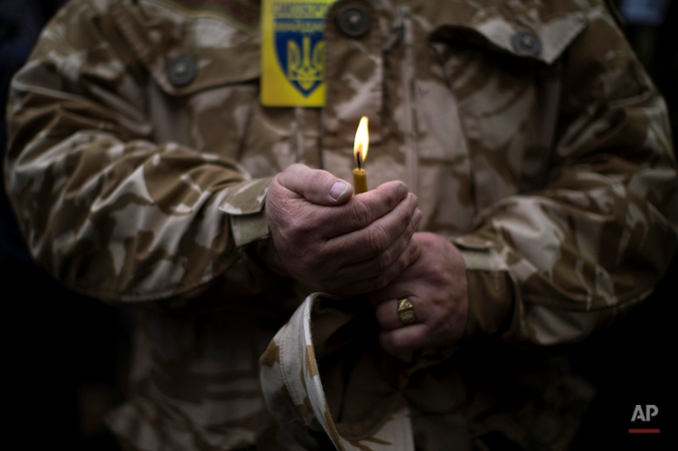 A man wearing camouflage uniform holds a candle during the funeral of Volodymyr Topiy, 59, who was found burned in the house of trade unions in Kiev's Independence Square during recent clashes with police, Ukraine, Tuesday, March 4, 2014. Vladimir Putin ordered tens of thousands of Russian troops participating in military exercises near Ukraine's border to return to their bases as U.S. Secretary of State John Kerry was on his way to Kiev. Tensions remained high in the strategic Ukrainian peninsula of Crimea with troops loyal to Moscow fired warning shots to ward off protesting Ukrainian soldiers. (AP Photo/Emilio Morenatti)