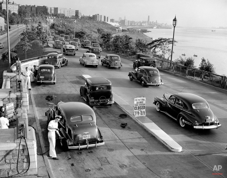 A gasoline station attendant on New York City's Henry Hudson Parkway glances at his watch as he serves the last customer before the 7 p.m. to 7 a.m. curfew, Aug. 3, 1941. A sign reminds the inbound motorists that the station is to close during the 12-hour period in response to the government request that sales be suspended in eastern seaboard states. (AP Photo)