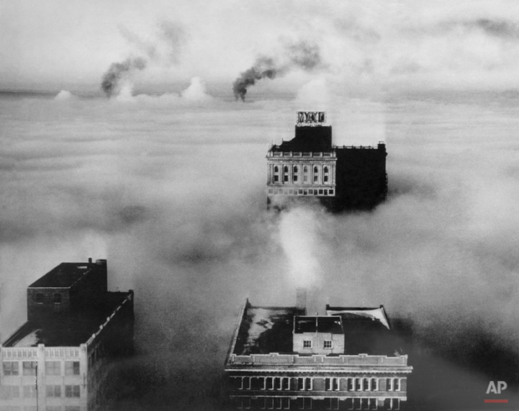 Only three buildings and several columns of smoke venture above this dense fog blanket which settled over Tulsa, Oklahoma, for a few minutes, reducing visibility to zero and tying up traffic, Jan. 15, 1944. The Mayor Hotel, center, is a 19-story structure. (AP Photo)