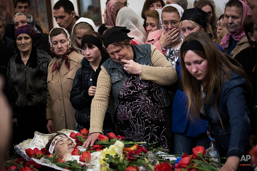 The mother of Sigarov Alexander, 24, reaches for his body at a church during the funeral for three people killed last Sunday in a shooting by unknown gunmen at a checkpoint, in Slovyansk, Ukraine, Tuesday, April 22, 2014. (AP Photo/Manu Brabo)