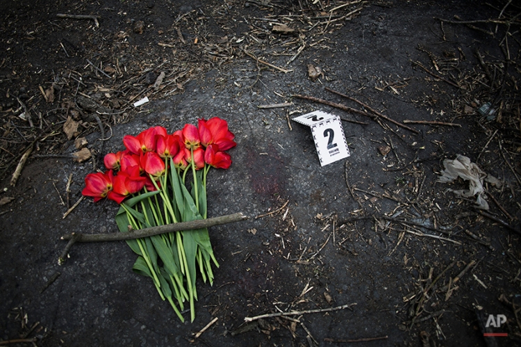 A bouquet is seen close to a bloodstain and a police evidence mark at pro Russia check point after a night fight between an unidentified masked man and pro-Russian activists in the village of Bulbasika near Slovyansk, Ukraine, Sunday, April 20, 2014.(AP Photo/Manu Brabo)