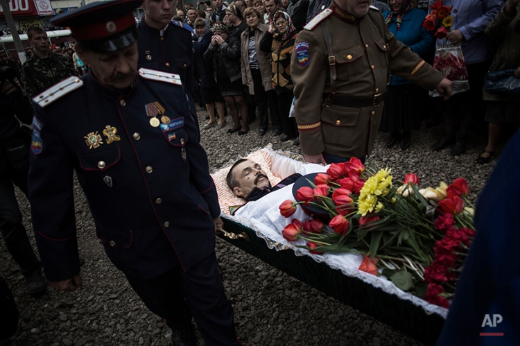 UkraineThe body of Pavel Pavelco, 42, a pro Russia militiaman, one of three people killed last Sunday in a shooting by unknown gunmen at a checkpoint, is carried by pallbearers to a church during a funeral in Slovyansk, Ukraine, Tuesday, April 22, 2014. (AP Photo/Manu Brabo)