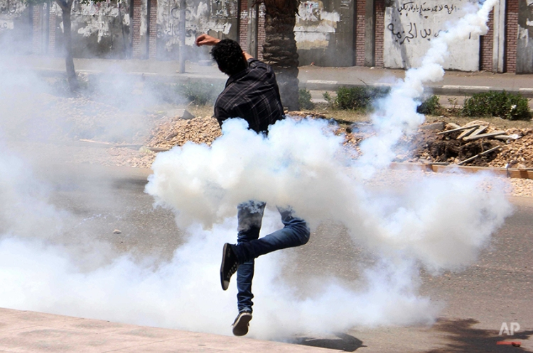 A bystander throws a tear gas canister that came back from the al-Azhar University campus after the canister was originally shot by the Egyptian security forces towards protesters at the school in Cairo, Egypt, Friday, May 2, 2014. Supporters of Egypt's Islamist President Mohammed Morsi continue to protest in the streets as retired Field Marshal Abdel-Fattah el-Sissi, who led last year's overthrow of Morsi, appears poised to win in the presidential election planned this month. (AP Photo/Mohammed Abu Zaid)