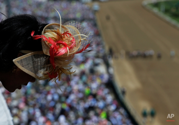 A woman looks out over a balcony before the 140th running of the Kentucky Derby horse race at Churchill Downs Saturday, May 3, 2014, in Louisville, Ky. (AP Photo/Charlie Riedel)