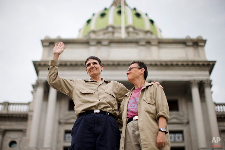 Plaintiffs in the lawsuit, Julie Lobur, left, and Marla Cattermole look out on supporters of gay marriage at a rally on the steps of the state Capitol Tuesday, May 20, 2014, in Harrisburg, Pa. Pennsylvania's ban on gay marriage was overturned Tuesday by a federal judge in a decision that makes same-sex marriage legal throughout the Northeast. (AP Photo/Matt Rourke)