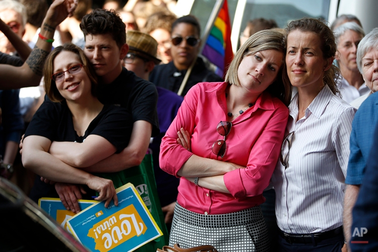From right, Viola Vetterm and her wife Kate Potalivo, and Amber Orion and her partner, Joy Payton listen to a speaker during a rally at City Hall, Tuesday, May 20, 2014, in Philadelphia. Pennsylvania's ban on gay marriage was overturned by a federal judge Tuesday. (AP Photo/Matt Slocum)