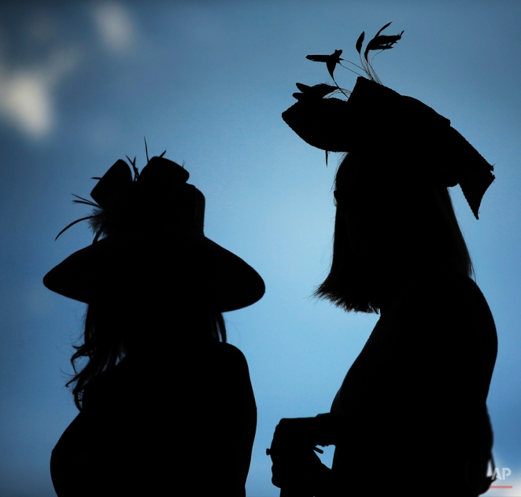 Women watch a race before the 140th running of the Kentucky Derby horse race at Churchill Downs Saturday, May 3, 2014, in Louisville, Ky. (AP Photo/Matt Slocum)