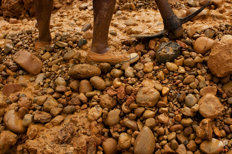 """In this May 21, 2014 photo, a miner with an axe digs for gold using a rustic technique known as """"chiquiquiar"""" in Huepetuhe in the Madre de Dios region of Peru. After a government crackdown on illegal mining companies in April, the miners who stayed behind are reduced to rudimentary gold extraction using pickaxes, shovels and small motors. (AP Photo/Rodrigo Abd)"""
