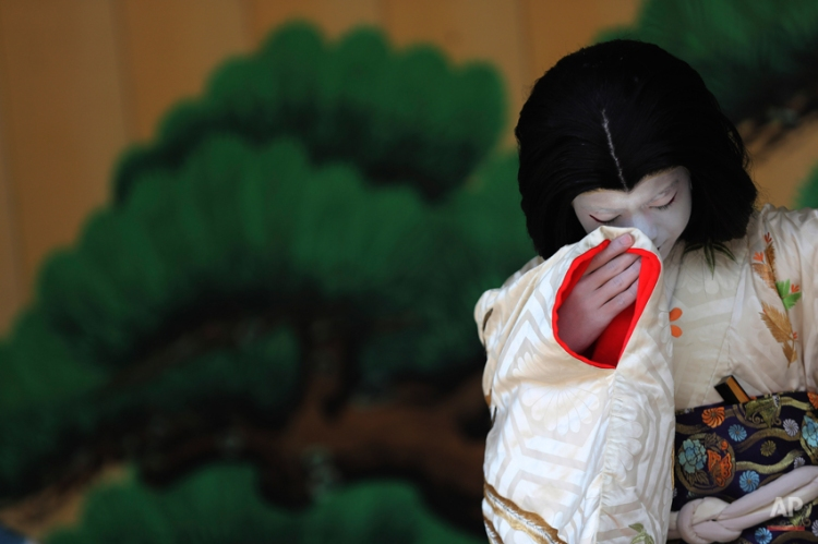 """A young boy acting as an old woman performs during a show of an amateur children kabuki theatrical company in Tokyo, Saturday, March 29, 2014. Kabuki is a Japanese classical theater performance and a male kabuki actor performs as an """"onnagata"""" female impersonator. (AP Photo/Eugene Hoshiko)"""
