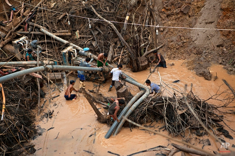 """In this May 5, 2014 photo, miners known as """"Maraqueros"""" ready a rustic type of hydraulic jet known locally as a """"Chupadera,"""" after hauling the device about 16-meters deep into a crater at a gold mine process in La Pampa in Peru's Madre de Dios region. A new threat now looms for the estimated 20,000 wildcat miners who toil in huge scar of denuded rainforest known as La Pampa, an area nearly three times the size of Washington, D.C. Peru's government declared all informal mining illegal on April 19 and began a crackdown. (AP Photo/Rodrigo Abd)"""