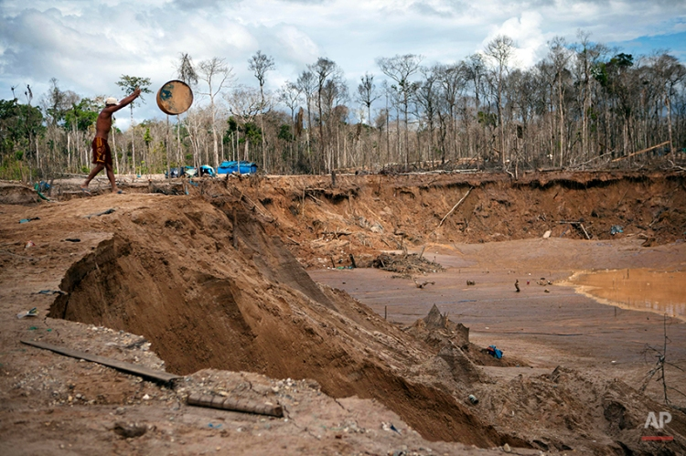 A man throws an empty drum into the crater made from gold mining in La Pampa in the Madre de Dios region in Peru, Friday, May 2, 2014. People at the illegal gold mine are working up to the last minute while they fear authorities will arrive any moment as part of a government crackdown since a nationwide ban on illegal gold mining took effect April 19. (AP Photo/Rodrigo Abd)