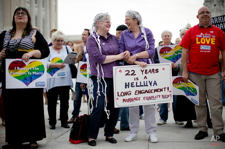 Peg Welch, center left, and her wife Delma Welch gather with others at a gay marriage rally on the steps of the state Capitol Tuesday, May 20, 2014, in Harrisburg, Pa. Pennsylvania's ban on gay marriage was overturned Tuesday by a federal judge in a decision that makes same-sex marriage legal throughout the Northeast. (AP Photo/Matt Rourke)