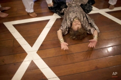 In this photo taken on Nov. 25, 2011, Rosa Cardoso, 89, lies on the floor during the 'Exu' and 'Pomba Gira' ceremony at an Umbanda house of worship in Rio de Janeiro, Brazil. Intolerance and outright hostility against Umbanda, as well as against Brazil's other major African-descended religion Candomble, have recently returned to the spotlight as religious-freedom activists cry foul over the demolition of a house known as Umbanda's birthplace. (AP Photo/Felipe Dana)