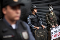 """An activist wearing a donkey mask stands next to police as they stand guard outside a military club during a protest in downtown Rio de Janeiro, Brazil, Thursday March 29, 2012. A club of retired military officers held its annual celebration of Brazil's 1964 military coup as usual, but faced protestors as members arrived for the event. Unlike its Latin American neighbors, Brazil never had a formal investigation into its 20-year dictatorship. The sign reads in Portuguese """" Father keep that one awayÖshut-up,"""" a play on words from a song by famous singer Chico Buarque which was censored during the dictatorship. (AP Photo/Felipe Dana)"""
