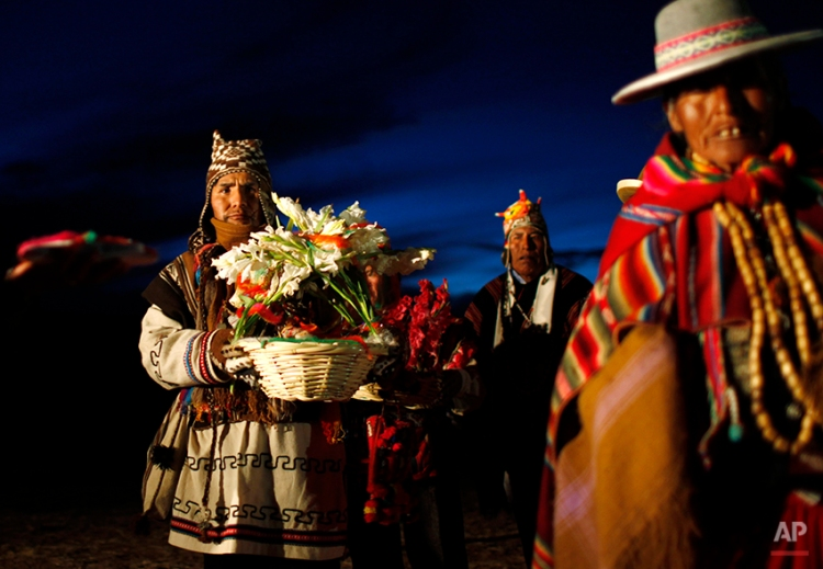 Andean religious leaders carry offerings to a new years ritual at the ruins of the ancient civilization of Tiwanaku located in the highlands in Tiwanaku, Bolivia, early Saturday, June 21, 2014. Bolivia's Aymara Indians are celebrating the year 5,522 as well as the Southern Hemisphere's winter solstice, which marks the start of a new agricultural cycle. (AP Photo/Juan Karita)