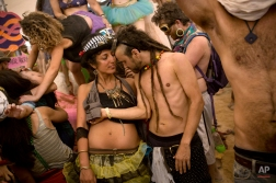 In this photo taken Thursday, June 5, 2014, Israelis dance at a party during Israel's first Midburn festival, modeled after the popular Burning Man festival held annually in the Black Rock Desert of Nevada, in the desert near the Israeli kibbutz of Sde Boker. Some came costumed in cape or corset. Others, from babies to grandparents, went nude. Participants brought their own food and water, and shared with others. The only thing on sale was ice because of the scorching heat. There were workshops in sculpture, drawing, and touch therapy. There was music and theater. At the 'tent of heaven and hell,' participants were chosen at random for one of two fates: getting massages or doing chores. (AP Photo/Oded Balilty)