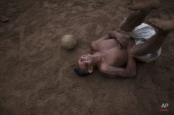 In this May 24, 2014, photo, a man reacts after being hit by the ball during a soccer game in the Tatuyo indigenous community near Manaus, Brazil. Manaus is one of the host cities for the 2014 World Cup in Brazil. (AP Photo/Felipe Dana)