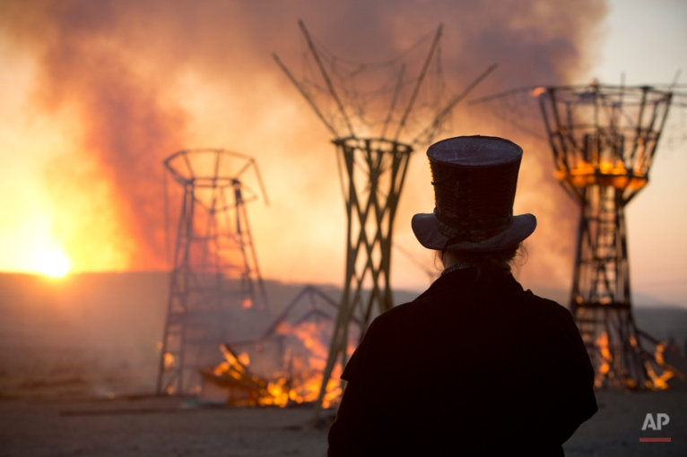 In this photo taken Saturday, June 7, 2014, a man looks at a wooden sculpture that was set on fire during Israel's first Midburn festival, modeled after the popular Burning Man festival held annually in the Black Rock Desert of Nevada, in the desert near the Israeli kibbutz of Sde Boker. Some 3,000 people set up a colorful encampment in the dusty moonscape, swinging from hoops by day and burning giant wooden sculptures by night. (AP Photo/Oded Balilty)