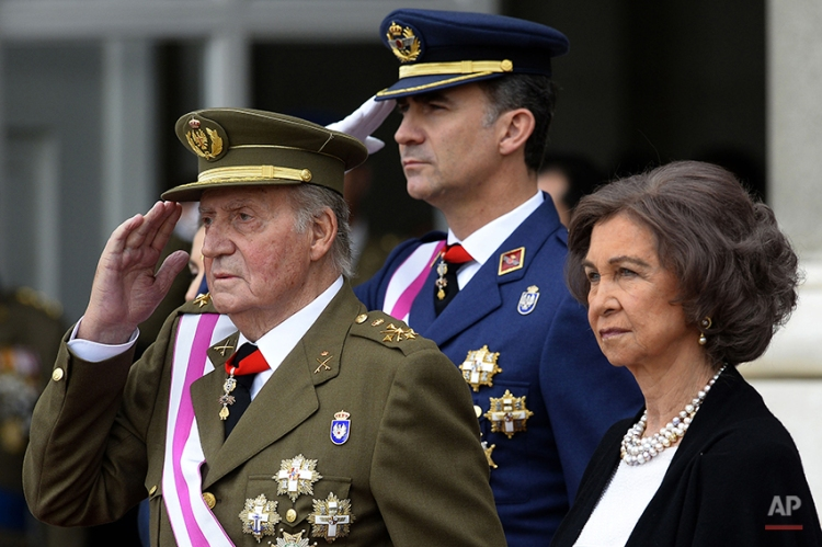 In this Monday, Jan. 6, 2014, file photo, Spain's Crown Prince Felipe, centre, Spain's King Juan Carlos, left, and Spain's Queen Sofia, right, attend the annual Pascua Militar Epiphany ceremony at the Royal Palace in Madrid, Spain. Spain's King Juan Carlos plans to abdicate and pave the way for his son, Crown Prince Felipe, to take over, Spanish Prime Minister Mariano Rajoy told the country Monday in an announcement broadcast nationwide. The 76-year-old Juan Carlos oversaw his country's transition from dictatorship to democracy but has had repeated health problems in recent years. (AP Photo/Gerard Julien, Pool, File)
