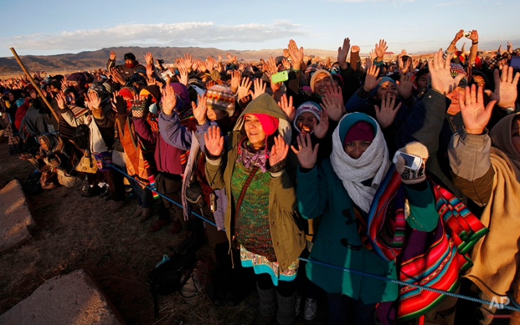 People hold up their hands to the first rays of sunlight during a new years ritual at the ruins of the ancient civilization of Tiwanaku located in the highlands in Tiwanaku, Bolivia, early Saturday, June 21, 2014. Bolivia's Aymara Indians are celebrating the year 5,522 as well as the Southern Hemisphere's winter solstice, which marks the start of a new agricultural cycle. (AP Photo/Juan Karita)