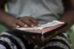 In this May 9, 2014 photo, a former drug user reads the bible at the God's Love rehabilitation center in Rio de Janeiro, Brazil. Pastor Celio Ricardo offers them a roof in a makeshift shelter in a nearby neighborhood, a simple structure next to his humble Love of God evangelical church. There, young men sleep side-by-side on plain raw-wood beds. Clean shirts hang from roof beams, meager belongings gathered tidily on battered dressers. (AP Photo/Felipe Dana)