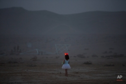 In this photo taken Wednesday, June 4, 2014, a young Israeli girl walks in the playa during Israel's first Midburn festival, modeled after the popular Burning Man festival held annually in the Black Rock Desert of Nevada, in the desert near the Israeli kibbutz of Sde Boker. Some came costumed in cape or corset. Others, from babies to grandparents, went nude. Participants brought their own food and water, and shared with others. The only thing on sale was ice because of the scorching heat. (AP Photo/Oded Balilty)