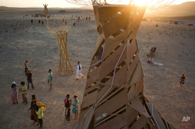 In this photo taken Friday, June 6, 2014, people, mostly Israelis, walk in the playa during Israel's first Midburn festival, modeled after the popular Burning Man festival held annually in the Black Rock Desert of Nevada, in the desert near the Israeli kibbutz of Sde Boker. Some 3,000 people set up a colorful encampment in the dusty moonscape, swinging from hoops by day and burning giant wooden sculptures by night. At the end, participants were told to remove their own trash and leave the desert without a trace.(AP Photo/Oded Balilty)
