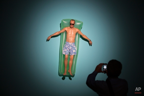 A visitor photographs a sculpture entitled 'Drift' by Australian artist Ron Mueck during the opening day of his exhibition at the Museum of Modern Art in Rio de Janeiro, Brazil, Wednesday, March 19, 2014. The exhibition will run from today to June 1, 2014. (AP Photo/Felipe Dana)