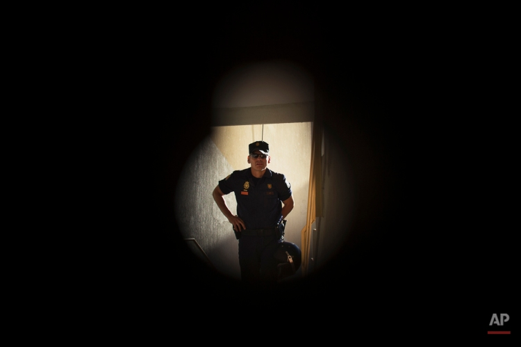 A riot police officer, seen through the keyhole, arrives to evict Juan Jose Munoz Escudero, 29 years old, and his family in Madrid, Spain, Monday, June 16, 2014. Juan Jose Munoz Escudero his wife Tamara de la Cruz Bermudez, 27 years old, and his one year old baby live with a low income coming from selling goods in the street and state benefits of 423 euros ($574). They occupied the apartment and have tried to negotiate to pay a low protected rent to the City Hall Housing and Land Company (EMVS) but the company demanded their eviction. EMVS, a state company with an aim to give housing solutions for people in need, sold 1.860 state apartments to private investors, last year. (AP Photo/Andres Kudacki)