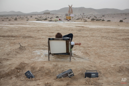 In this photo taken Wednesday, June 4, 2014, an Israeli man rests on a couch during Israel's first Midburn festival, modeled after the popular Burning Man festival held annually in the Black Rock Desert of Nevada, in the desert near the Israeli kibbutz of Sde Boker. Some 3,000 people set up a colorful encampment in the dusty moonscape, swinging from hoops by day and burning giant wooden sculptures by night. (AP Photo/Oded Balilty)