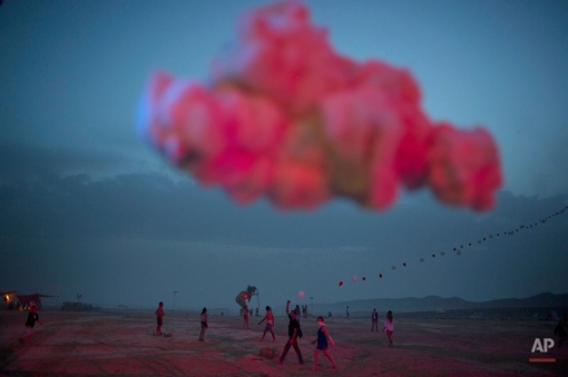 In this photo taken Wednesday, June 4, 2014, Israelis walk in the playa during the Israel's first Midburn festival, modeled after the popular Burning Man festival held annually in the Black Rock Desert of Nevada, in the desert near the Israeli kibbutz of Sde Boker. Some 3,000 people set up a colorful encampment in the dusty moonscape, swinging from hoops by day and burning giant wooden sculptures by night. (AP Photo/Oded Balilty)