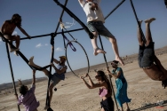 """In this photo taken Friday, June 6, 2014, Israelis climb on one of the art installation during Israel's first Midburn festival, modeled after the popular Burning Man festival held annually in the Black Rock Desert of Nevada, in the desert near the Israeli kibbutz of Sde Boker. Some 3,000 people set up a colorful encampment in the dusty moonscape, swinging from hoops by day and burning giant wooden sculptures by night. For five days, participants mostly Israelis created a temporary city dedicated to creativity, communal living, and what the festival calls """"radical self-expression"""". (AP Photo/Oded Balilty)"""