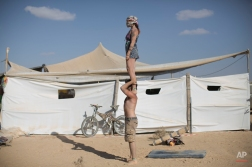 """In this photo taken Friday, June 6, 2014, Israeli acrobats perform during Israel's first Midburn festival, modeled after the popular Burning Man festival held annually in the Black Rock Desert of Nevada, in the desert near the Israeli kibbutz of Sde Boker. Some 3,000 people set up a colorful encampment in the dusty moonscape, swinging from hoops by day and burning giant wooden sculptures by night. For five days, participants mostly Israelis created a temporary city dedicated to creativity, communal living, and what the festival calls 'radical self-expression"""". (AP Photo/Oded Balilty)"""