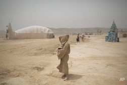 In this photo taken Wednesday, June 4, 2014, an Israeli man walks in the playa during Israel's first Midburn festival, modeled after the popular Burning Man festival held annually in the Black Rock Desert of Nevada, in the desert near the Israeli kibbutz of Sde Boker. Some 3,000 people set up a colorful encampment in the dusty moonscape, swinging from hoops by day and burning giant wooden sculptures by night. (AP Photo/Oded Balilty)