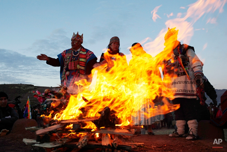Andean religious leaders perform a new year ritual at the ruins of the ancient civilization of Tiwanaku located in the highlands in Tiwanaku, Bolivia, early Saturday, June 21, 2014. Bolivia's Aymara Indians are celebrating the year 5,522 as well as the Southern Hemisphere's winter solstice, which marks the start of a new agricultural cycle. (AP Photo/Juan Karita)