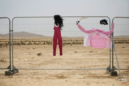 In this photo taken Wednesday, June 4, 2014, costumes hang on a fence at the first Israel's Midburn festival, modeled after the popular Burning Man festival held annually in the Black Rock Desert of Nevada, in the desert near the Israeli kibbutz of Sde Boker. The festival took place a few miles southwest of the desert gravesite of Israel's founding father, David Ben-Gurion, who dreamed of making the Negev desert bloom _ though he probably didn't envisioned it blossoming with hula hoops and pyrotechnics. At the end, participants were told to remove their own trash and leave the desert without a trace. (AP Photo/Oded Balilty)