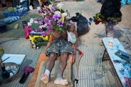 """In this photo taken Saturday, June 7, 2014, an Israeli man holds flowers during Israel's first Midburn festival, modeled after the popular Burning Man festival held annually in the Black Rock Desert of Nevada, in the desert near the Israeli kibbutz of Sde Boker. Some 3,000 people set up a colorful encampment in the dusty moonscape, swinging from hoops by day and burning giant wooden sculptures by night. For five days, participants mostly Israelis created a temporary city dedicated to creativity, communal living, and what the festival calls """"radical self-expression"""". (AP Photo/Oded Balilty)"""