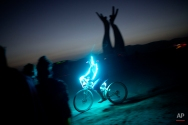 """In this photo taken Thursday, June 5, 2014, An Israeli man rides a bicycle as the sun goes down during Israel's first Midburn festival, modeled after the popular Burning Man festival held annually in the Black Rock Desert of Nevada, in the desert near the Israeli kibbutz of Sde Boker. For five days, participants _ mostly Israelis _ created a temporary city dedicated to creativity, communal living and what the festival calls """"radical self-expression."""" (AP Photo/Oded Balilty)"""