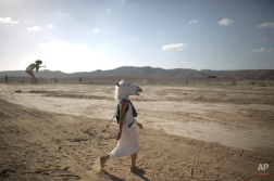 """In this photo taken Friday, June 6, 2014, An Israeli woman wears a unicorn mask as she walks in the playa during Israel's first Midburn festival, modeled after the popular Burning Man festival held annually in the Black Rock Desert of Nevada, in the desert near the Israeli kibbutz of Sde Boker. Some 3,000 people set up a colorful encampment in the dusty moonscape, swinging from hoops by day and burning giant wooden sculptures by night. For five days, participants mostly Israelis created a temporary city dedicated to creativity, communal living, and what the festival calls """"radical self-expression."""" (AP Photo/Oded Balilty)"""