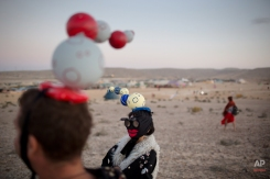 In this photo taken Friday, June 6, 2014, Israelis in costumes walk around the playa during Israel's first Midburn festival, modeled after the popular Burning Man festival held annually in the Black Rock Desert of Nevada, in the desert near the Israeli kibbutz of Sde Boker. For the Bedouin Arab shepherds tending their flocks in Israelís Negev desert last week, it was almost as if aliens had landed from outer space. (AP Photo/Oded Balilty)