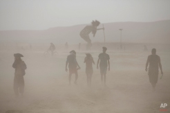 """In this photo taken Thursday, June 5, 2014, people walk in the dusty playa during Israel's first Midburn festival, modeled after the popular Burning Man festival held annually in the Black Rock Desert of Nevada, in the desert near the Israeli kibbutz of Sde Boker. For five days, participants, mostly Israelis, created a temporary city dedicated to creativity, communal living, and what the festival calls""""radical self-expression."""" (AP Photo/Oded Balilty)"""