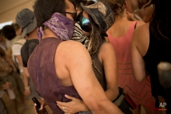 """In this photo taken Thursday, June 5, 2014, Israelis kiss at a party during Israel's first Midburn festival, modeled after the popular Burning Man festival held annually in the Black Rock Desert of Nevada, in the desert near the Israeli kibbutz of Sde Boker. Some 3,000 people set up a colorful encampment in the dusty moonscape, swinging from hoops by day and burning giant wooden sculptures by night. For five days, participants mostly Israelis created a temporary city dedicated to creativity, communal living, and what the festival calls """"radical self-expression"""". (AP Photo/Oded Balilty)"""