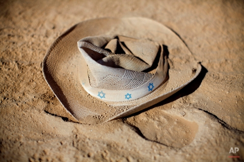In this photo taken Friday, June 6, 2014, a hat with stars of david lays on the ground during Israel's first Midburn festival, modeled after the popular Burning Man festival held annually in the Black Rock Desert of Nevada, in the desert near the Israeli kibbutz of Sde Boker. The festival took place a few miles southwest of the desert gravesite of Israel's founding father, David Ben-Gurion, who dreamed of making the Negev desert bloom _ though he probably didn't envisioned it blossoming with hula hoops and pyrotechnics. At the end, participants were told to remove their own trash and leave the desert without a trace. (AP Photo/Oded Balilty)