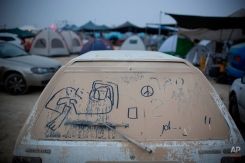 """In this photo taken Wednesday, June 4, 2014, hand writing and doodles adorn a dusty car during Israel's first Midburn festival, modeled after the popular Burning Man festival held annually in the Black Rock Desert of Nevada, in the desert near the Israeli kibbutz of Sde Boker. For five days, participants _ mostly Israelis _ created a temporary city dedicated to creativity, communal living and what the festival calls """"radical self-expression."""" (AP Photo/Oded Balilty)"""