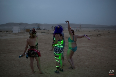 """In this photo taken Wednesday, June 4, 2014, Israelis dance at a party during Israel's first Midburn festival, modeled after the popular Burning Man festival held annually in the Black Rock Desert of Nevada, in the desert near the Israeli kibbutz of Sde Boker. Some 3,000 people set up a colorful encampment in the dusty moonscape, swinging from hoops by day and burning giant wooden sculptures by night. For five days, participants mostly Israelis created a temporary city dedicated to creativity, communal living, and what the festival calls """"radical self-expression"""". (AP Photo/Oded Balilty)"""